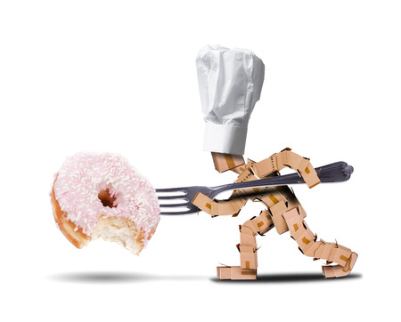 Chef box character with hat and a large fork attacking a large donut witha bite taken out of it. White background diet and food concept