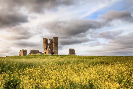 Old ancient ruined church set in a yellow crop landscape with beautiful clouds and sunset sunlight Stock Photo