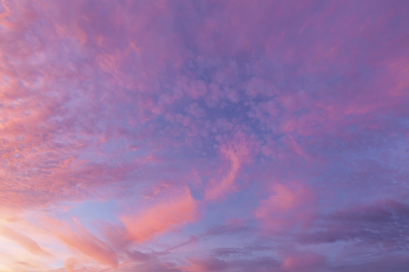 Pink clouds and blue sky background show natures calm weather and sunset glow landscape