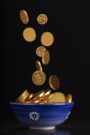 Pot of gold concept with chocolate gold coins falling in to a pot on a black background