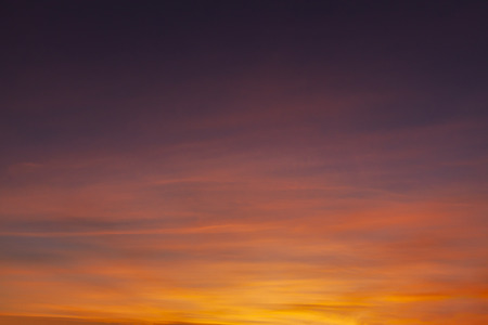 Stunning sunset sky with orange and red wispy clouds fading to dark skies above. Reklamní fotografie