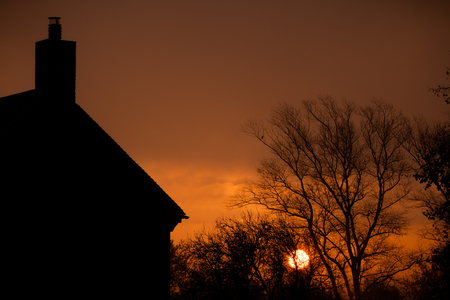 Sunrise at home. Early morning sun glowing through misty morning autumn trees.  Relaxing rural landscape at dawn with an orange sun rising behind a silhouette of a house and bare trees. Reklamní fotografie