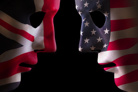 USA and GB face off head to head concept with human mask outlines covered in national flags symbols. Black background space for text