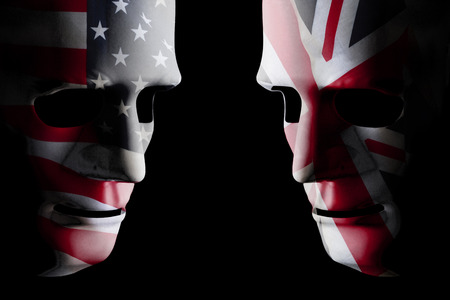 USA and GB face off head to head with human shaped masks covered with national flags. Black background space for text
