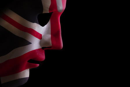 Face mask profile with a union jack flag texture looking down on a black blackground. Space for text