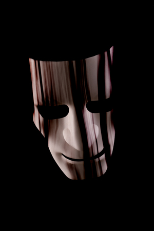 Scary face mask with hair hanging over face. Dark black background. Halloween or horror or underground crime concept