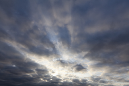 Cloudy sky with sun breaking through. Cloudscape nature background