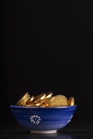 pot of gold coins with black background. Blue dish with fake chocolate money. Rich wealth concept Stok Fotoğraf
