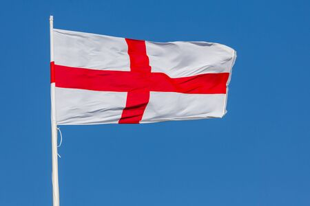 St. George flag of England flying in the wind on a flagpole with blue sky. Red cross on white background