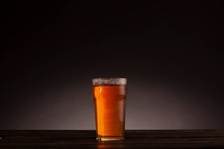 Pint of beer still life setup with dark table and minimal lighting. Dark background with copy space and text space.