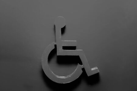 Disability symbol in black on a black background stylish simple logo design with text space 免版税图像