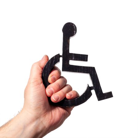 Disabled symbol being held up my a human hand. Power to disabled people sign on a white background 免版税图像