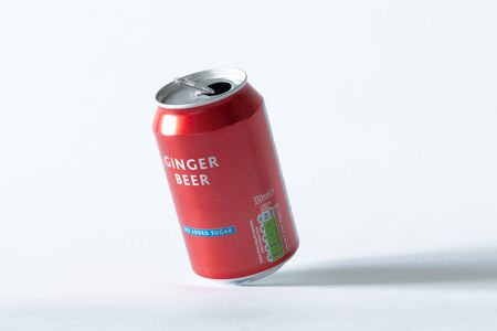An opened can of ginger beer on a white isolated background. Drink and recycling concept.