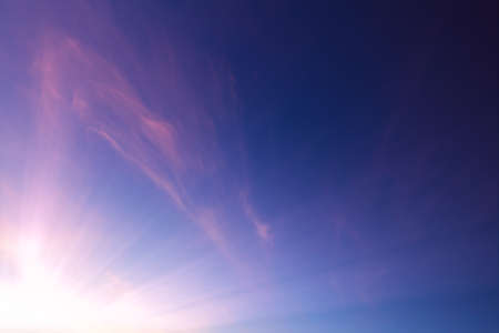 Pink wispy clouds in a blue sky sunset 免版税图像