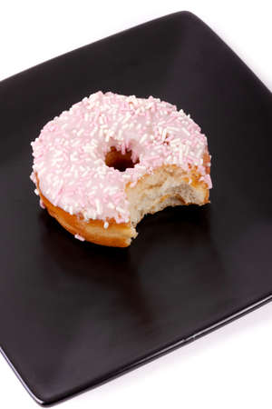 Frosted donut with a bite taken out of it, on a black square plate, with a white background.