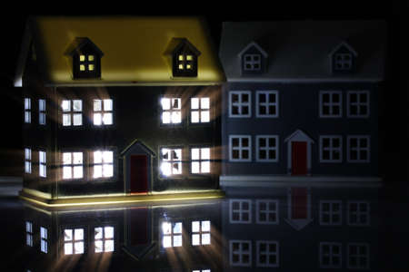 Toy house at night with the lights on indoors 免版税图像