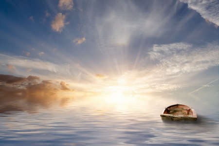 Lost at sea, old rowing boat bobbing around at sea in a tranquil sunset with calm ocean water. No land only seascape and beautiful clouds.