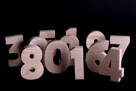 Large random wooden numbers standing up overlapping. Hardwood characters on a black background with copy space