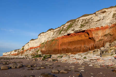Hunstanton cliffs in North Norfolk viewed from the beach. March 2017. These eroding cliffs expose a mid-Cretaceous sequence from the Albian to the succeeding Cenomanian around 100 million years ago, with exceptionally rich Albian ammonite fossils