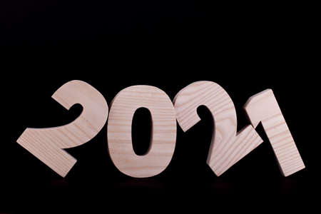2021 year large wooden numbers tilted and leaning. Hardwood characters on a black background
