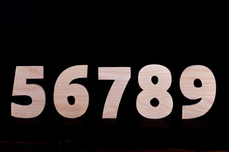 Large wooden numbers 5 6 7 8 9. Hardwood characters on a black background