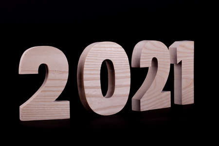 2021 year large wooden numbers at an angle. Hardwood characters on a black background