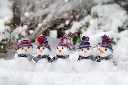 Five little cute snowmen dressed in hats and scarfs sat in the snow in winter. Cold and freezing snowing weather. Christmas holiday background