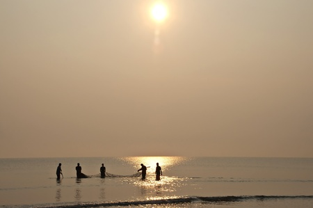A group of men fishing at sunrise Stock Photo