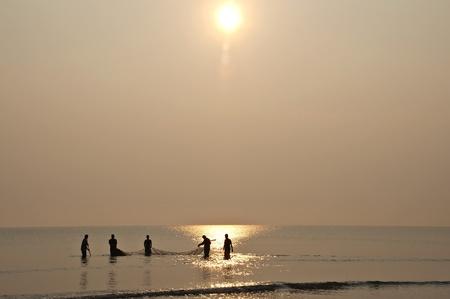 fishing nets: A group of men fishing at sunrise Stock Photo