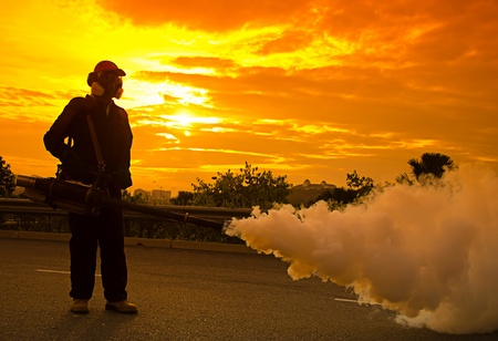 disease control: Environmental health workers are fogging to control dengue during sunset Stock Photo