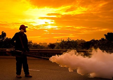環保衛生工作者霧日落期間控制登革熱 版權商用圖片