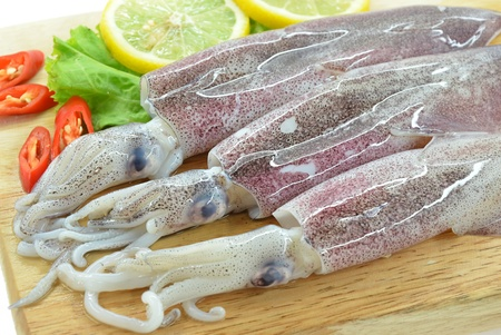 Fresh raw calamari and lemon on chopping board