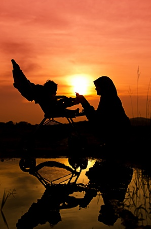 Muslim mother playing with her baby during sunset at park photo