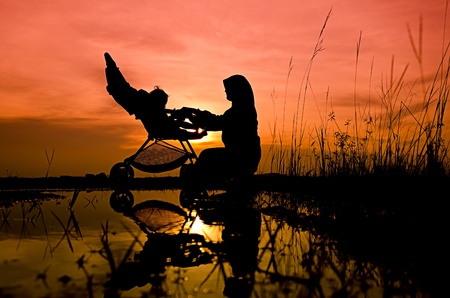 muslim baby: Muslim mother playing with her baby during sunset at park Stock Photo