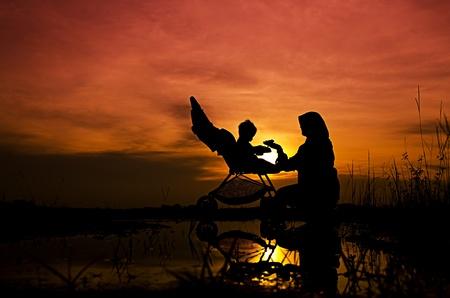공원에서 일몰 동안 그녀의 아기와 함께 재생 이슬람 어머니