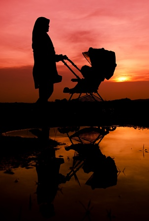 Muslim mother and baby walking during sunset with stroller  photo