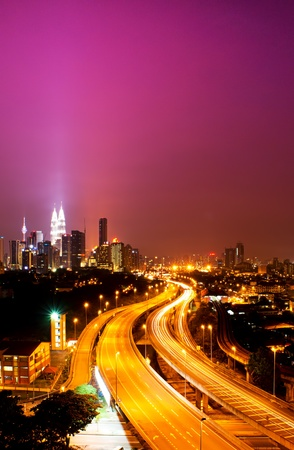 Kuala Lumpur twin towers with stunning light trail from the busy highway traffic