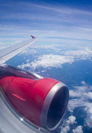 View out of airplane wing in flight Morning golden light below the clouds and blue sky Stock Photo - 13594319