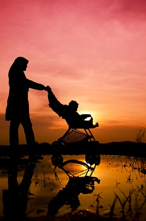 muslim baby: Muslim mother and baby walking during sunset with stroller