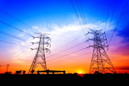 Silhouette electricity pylons during sunset