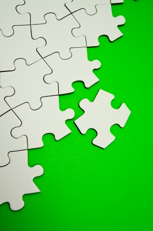 Jigsaw puzzle on green background photo