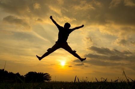 estrella de la vida: Silueta del hombre que salta en la puesta del sol