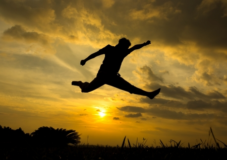 Silhouette of man jumping during sunset photo