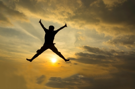 Silhouette of man jumping during sunset  Stock Photo