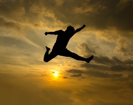 eternal life: Silhouette of man jumping during sunset  Stock Photo