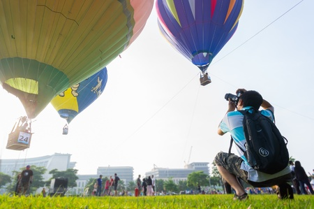 sightsee: PUTRAJAYA,MALAYSIA-MAC 30 :Unidentified photographer shoot hot air balloons at the 5th Putrajaya International Hot Air Balloon Fiesta March 30,2013 in Putrajaya.18 participants from various countries participated in the fiesta. Editorial