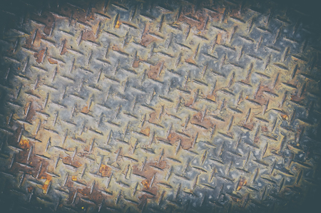 Rusty chequer plate close up in old film photography with vignette and grains effect