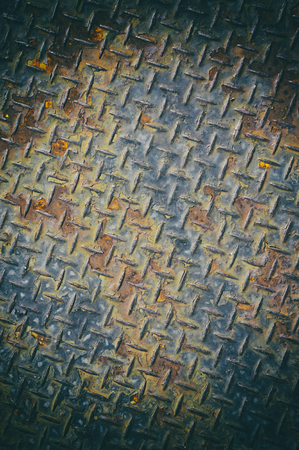 treadplate: Rusty chequer plate close up in old film photography with vignette and grains effect