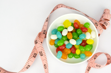 lose up: Colorful candies and tape measure with shallow depth of field (dof)-diet and healthy teeth concept Stock Photo