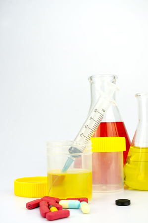 Urine sample bottle, pills and syringe isolated on a white background with shallow depth of field (dof) Stock Photo